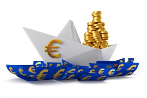 Conceptual paper boat floating in the euro currency and carries a large pile of coins isolated on a white background